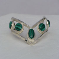 Five fouteen by ten millimeter oval Malachite Stone bezel set connected by two triangular wires which are formed to a chevron shape. Worn with chevron pointing down